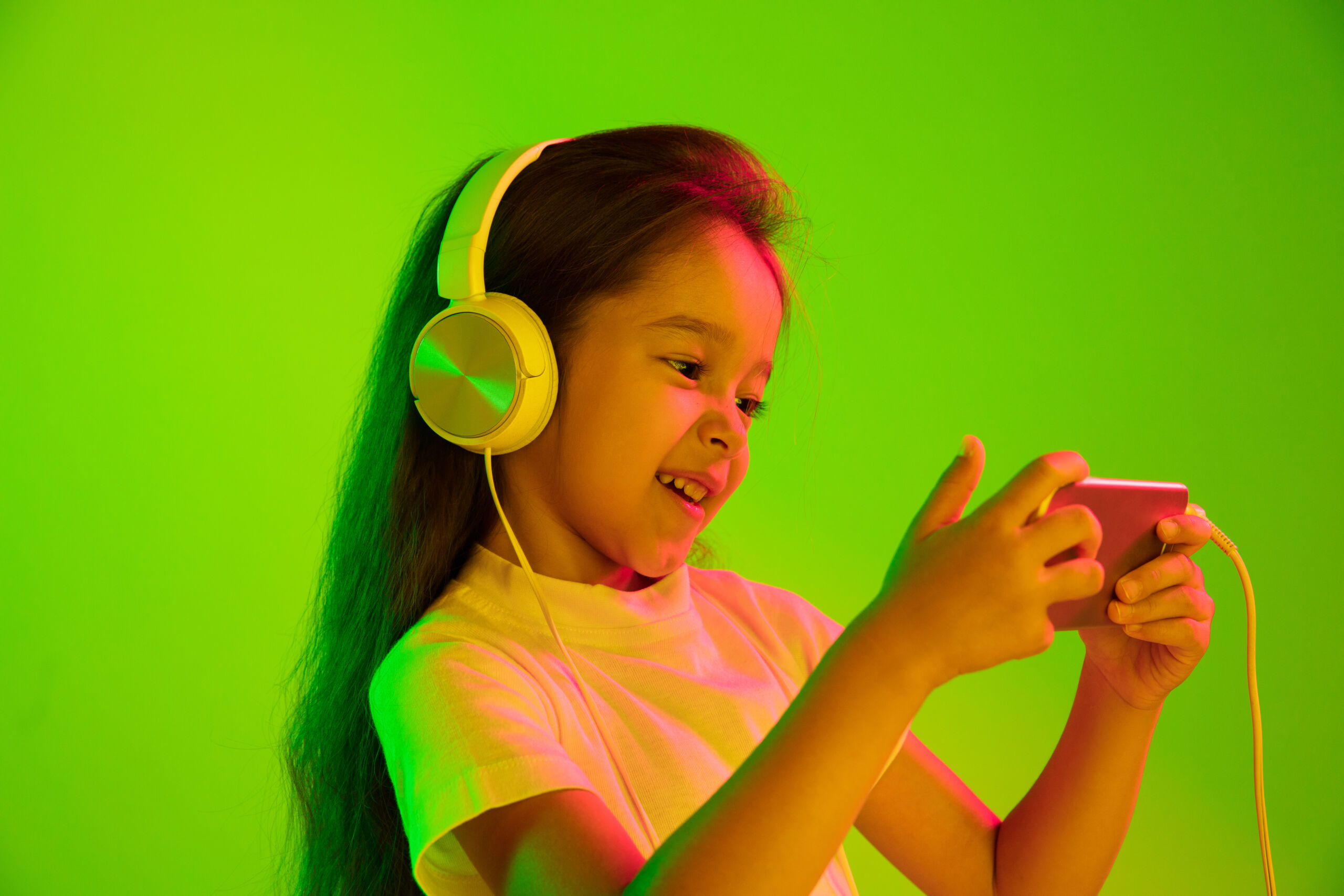 beautiful female half length portrait isolated on green wall in neon light young emotional girl human emotions facial expression concept using smartphone for vlog selfie chating gaming scaled